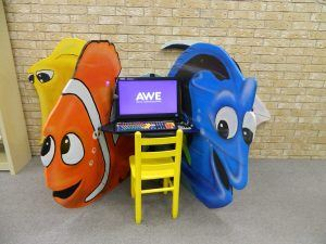 The Early Literacy Station sits on a small desk between large representations of colorful fish.
