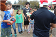 Officer Handing out Toys to Group of Children