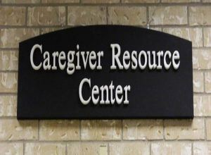 A black sign reads Caregiver Resource Center in white type.