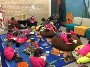 Children sit on the floor and beanbags, reading books.