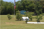A flagpole stands next to a sign and trees at Centennial Park.